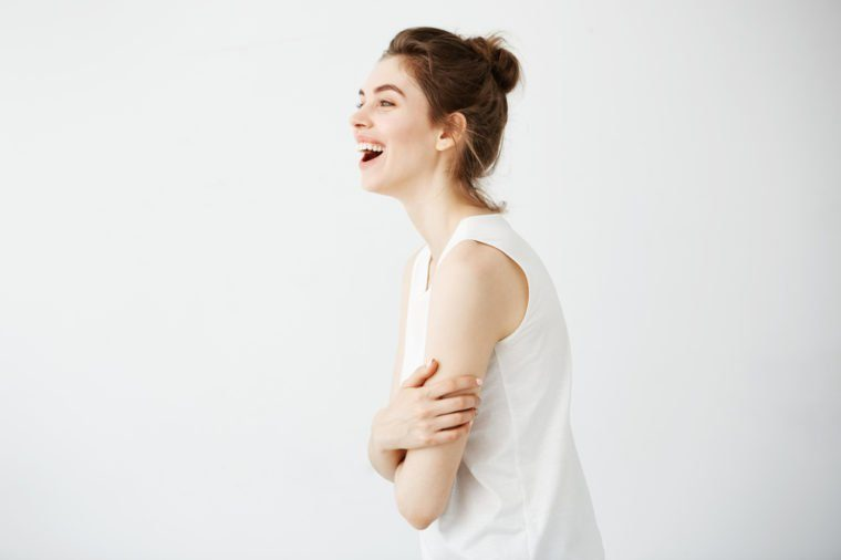 Happy cheerful young girl with bun smiling laughing over white background. Crossed arms.