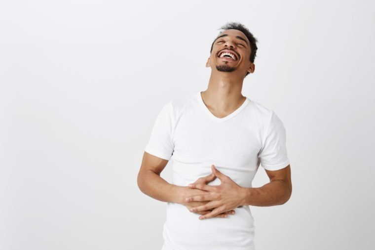 What nice time to live. Portrait of carefree attractive male student in white t-shirt, hearing funny joke, laughing out loud, feeling pain in belly muscles from chuckle, standing over gray wall