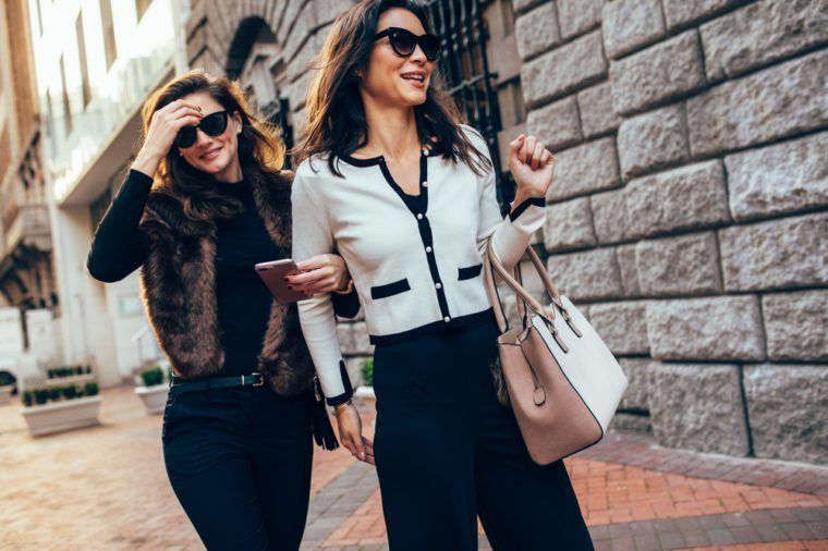 Two women walking together on the street. Female friends walking on the sidewalk by the road in the city.