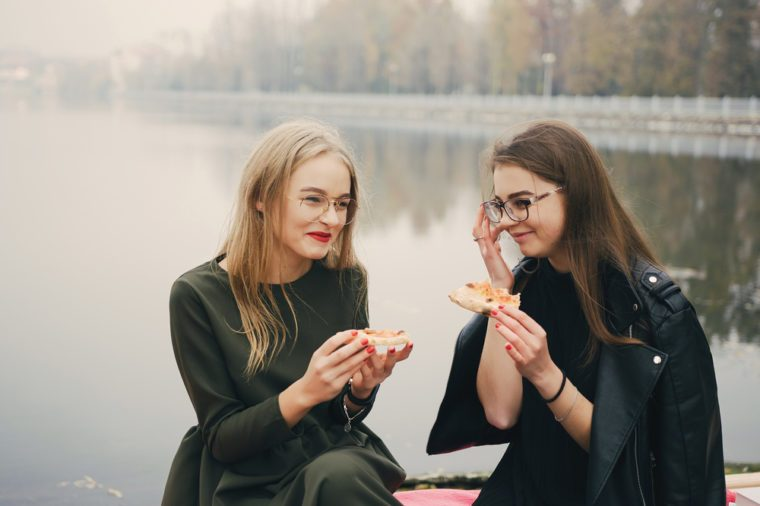 two young and stylish girls walking in the autumn park near water and eating pizza