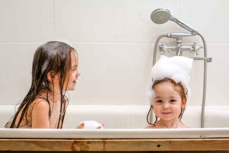 Two little sisters play in a bath with foam. They are very cheerful and lovely.