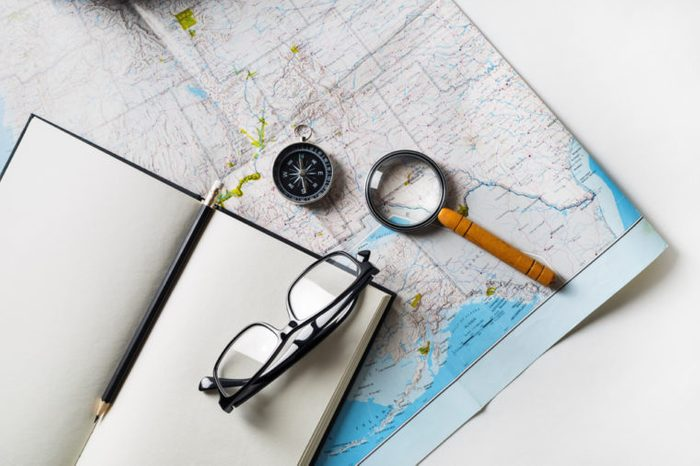 Travel plan background. Ready for the trip. Map, blank notebook, magnifier, compass, glasses and pencil. Flat lay