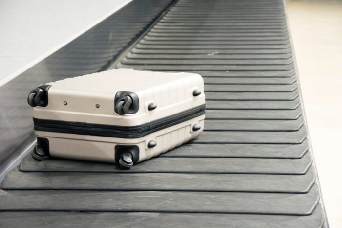 Wheeled suitcase on a luggage belt at the airport terminal.