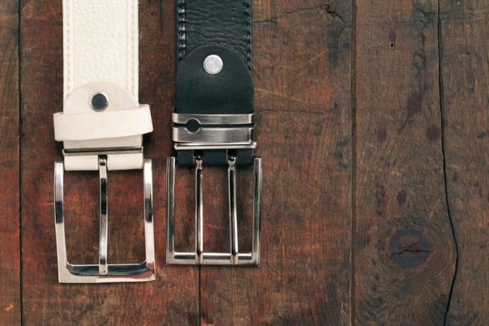 White and black leather belts hanging on old wooden background