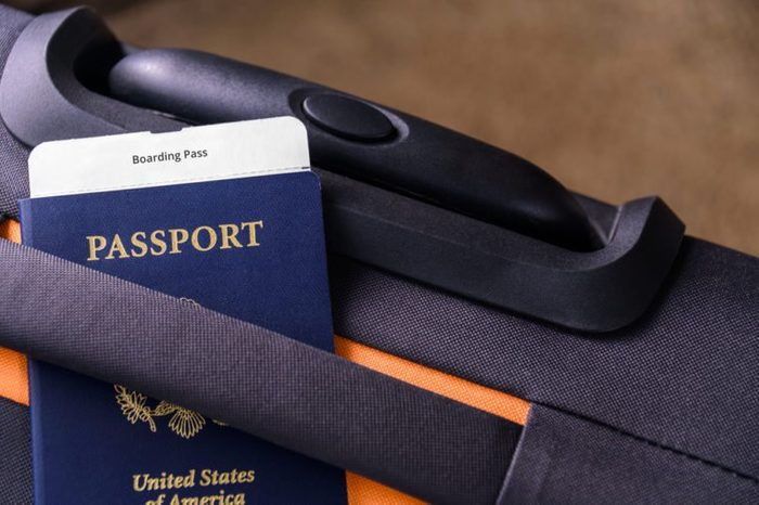 US passport and a boarding pass on a suitcase