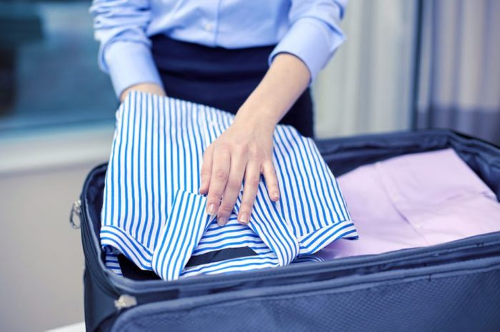 business, trip, luggage and people concept - close up of businesswoman packing clothes into travel bag