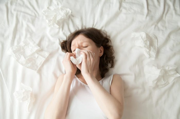 Young depressed or sick with flu model lying on the bed with closed eyes and blowing her nose into tissue. View from above