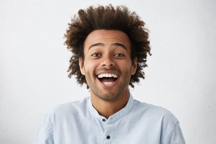 Carefree joyful handsome Afro American man with bushy hairstyle and bristle having shining eyes opening his mouth with joy bursting into laughing. Positive human expressions, emotions and feelings