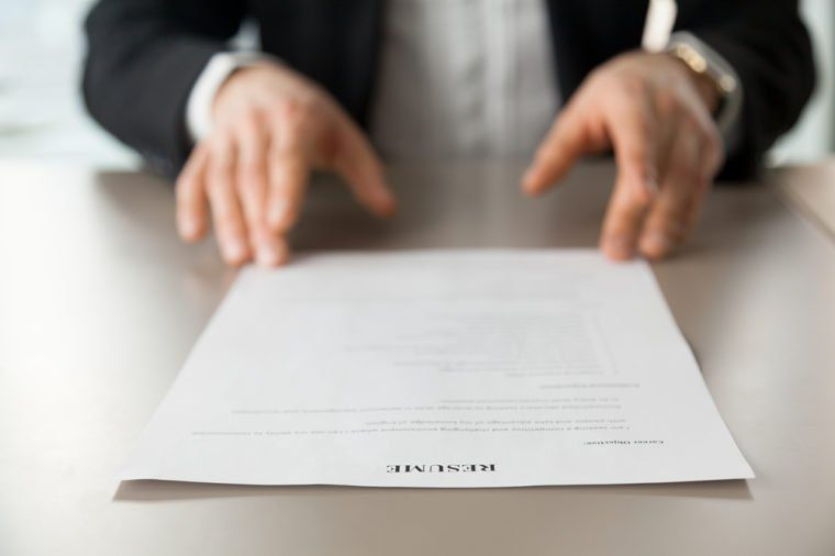 Resume document with guys hands in background. Recruitment manager reads resume. Job applicant offers CV to recruiter at interview. Employer examines achievements of new company worker. Close up photo
