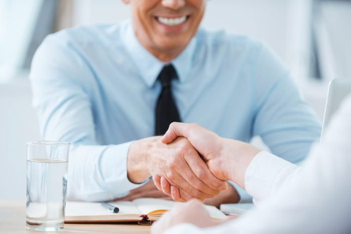 Sealing a deal. Close-up of two business people shaking hands while sitting at the working place