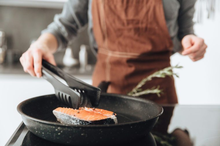 Cropped image of young lady standing in kitchen while cooking fish.
