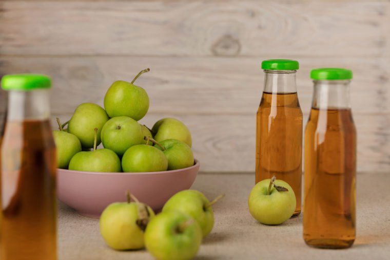 Green apples in a lilac plate and a bottle of apple juice on a wooden light background. Selective focus.