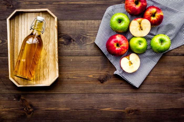 Bottle of fresh cider near autumn apples. Dark wooden background top view space for text