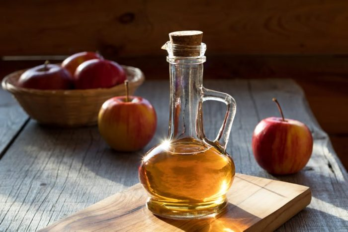 A bottle of apple cider vinegar in the morning sun, with apples in the background