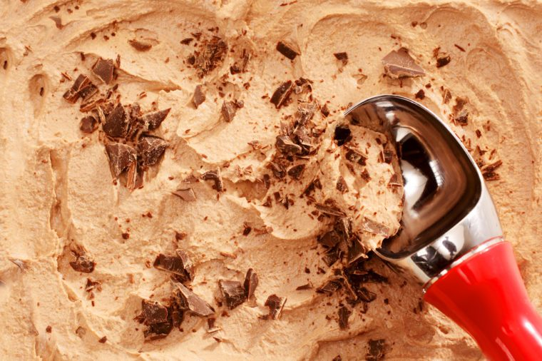 High Angle Close Up View of Red Handled Scoop Serving Mocha or Coffee Flavored Ice Cream Topped with Chocolate Shavings