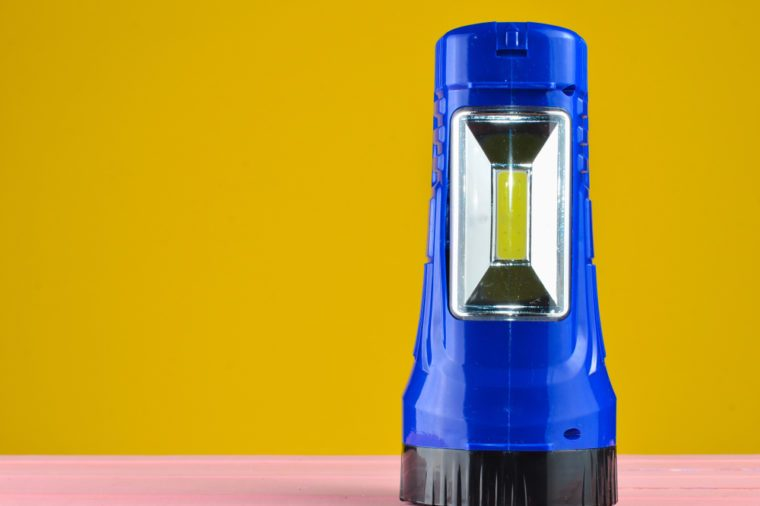 Blue flashlight projector lies on a desk isolated on a yellow wall