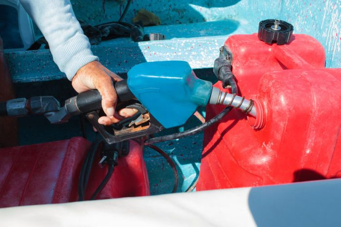 Close-up shot of a man fueling red plastic tank of a motor boat with petrol