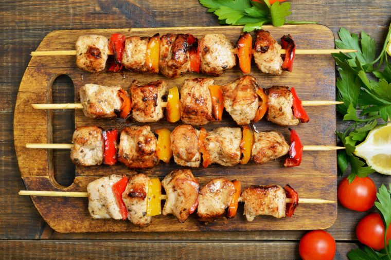 Grilled chicken kebabs on wooden cutting board, top view