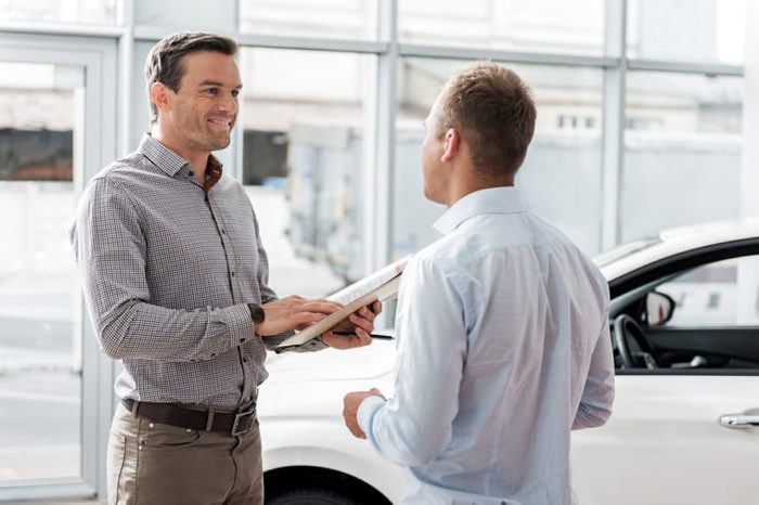 Outgoing man telling with worker in car dealership