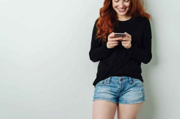 Pretty smiling young woman reading an sms or text message on her mobile phone with a smile in a close up cropped view