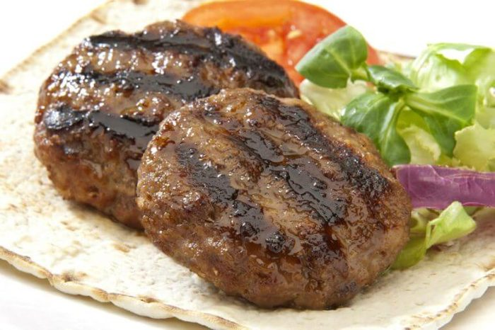 two burgers with salad on a pita