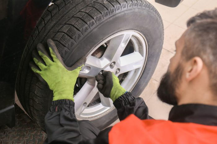 Professional mechanic changing tire in car service center