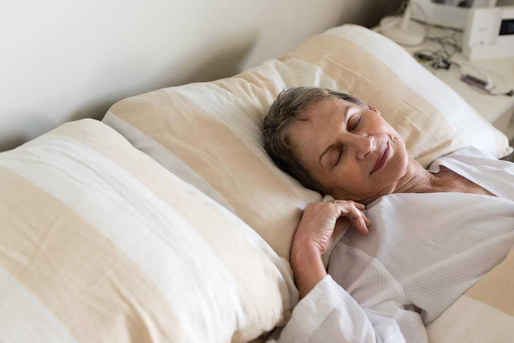 HIgh angle cropped view of elderly woman sleeping in bed (selective focus)