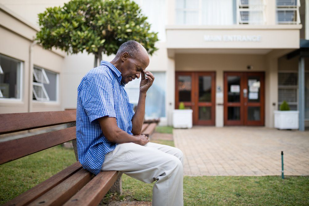 Sad senior man sitting on wooden bench outside nursing home