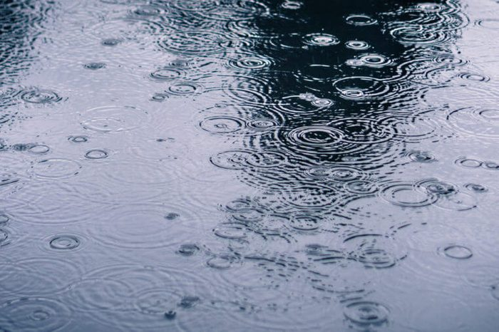 Rain drops rippling in a puddle on a dark, rainy day
