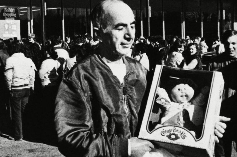 """A happy customer displays his newly purchased """"Cabbage Patch Kid"""" doll on as he leaves a south Bellingham, Mass. storefront crowded with people hoping to make similar, purchases. The moon faced cloth dolls, made by Coleco, have created quite a stir among shoppers nation wide, with some people waiting in 5-hour lines to buy them"""