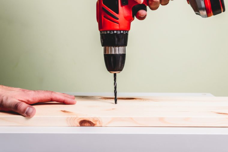 Power drill drilling screw into piece of wood