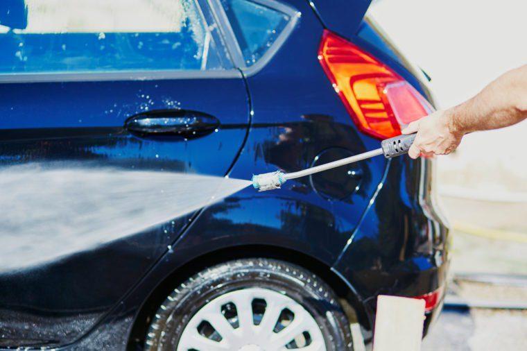 Manual vehicle washing on a car wash, closeup on washer's hand