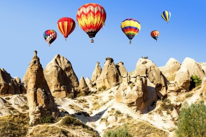 Balloons over the volcanic mountain landscape of Cappadocia in a bright sunny day