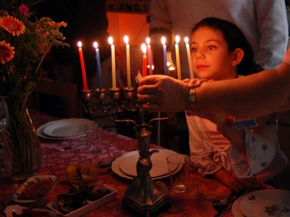 Jewish family lighting their menorah