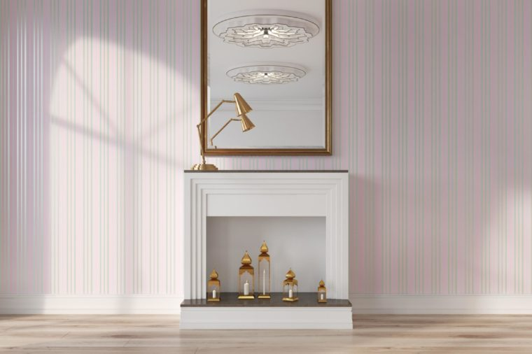 Pink living room interior with a white decorative fireplace, candles and a mirror on a wall. 3d rendering mock up