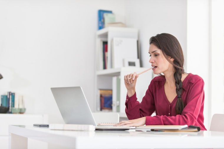 Woman chewing on pen at work