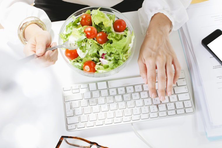 Eating healthy salad for lunch at desk