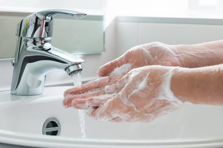 Washing hands in bathroom sink