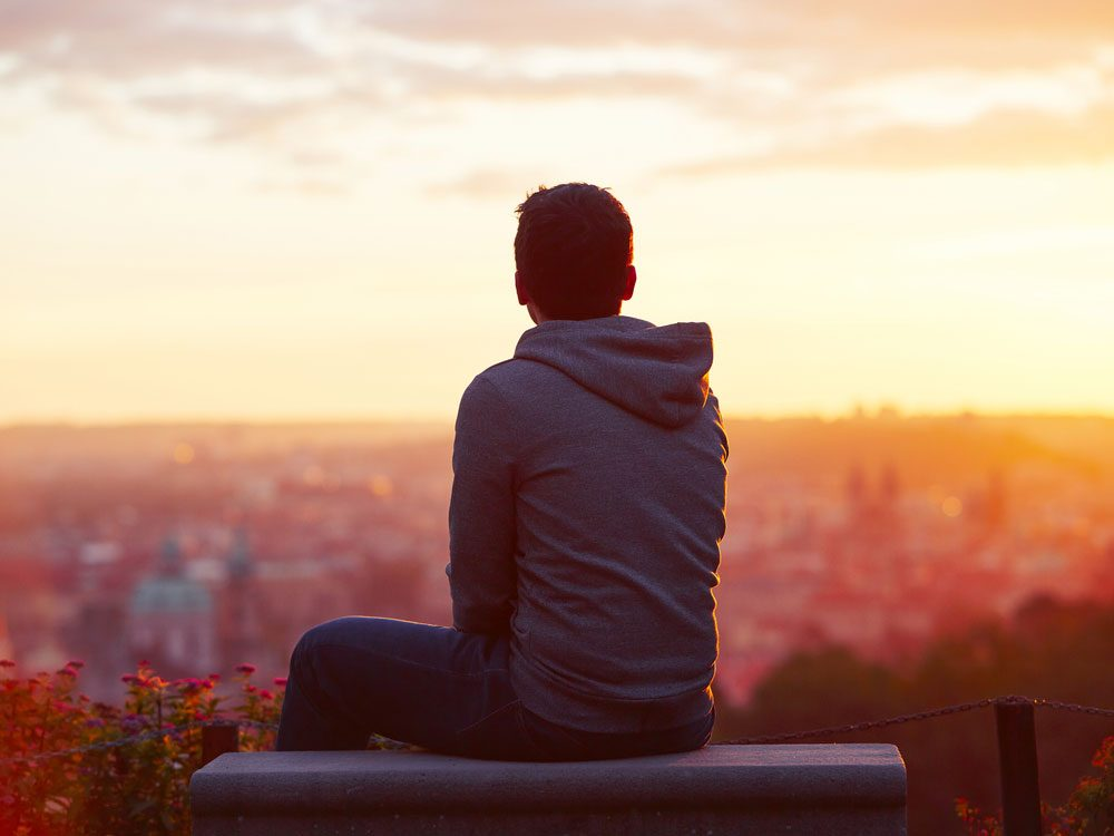 Man watching sunrise over city skyline