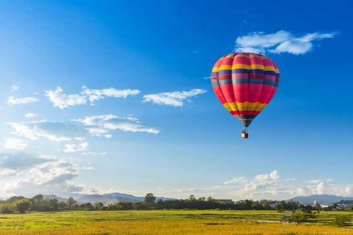 hot air balloon over the green paddy field. Composition of nature and blue sky background