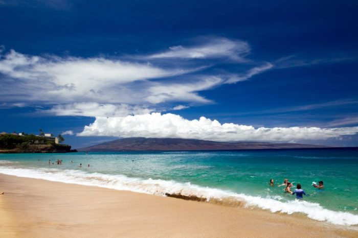 Tourists enjoying the beach at Kaanapali Beach on Maui with view towards Lanai in Hawaii, USA.