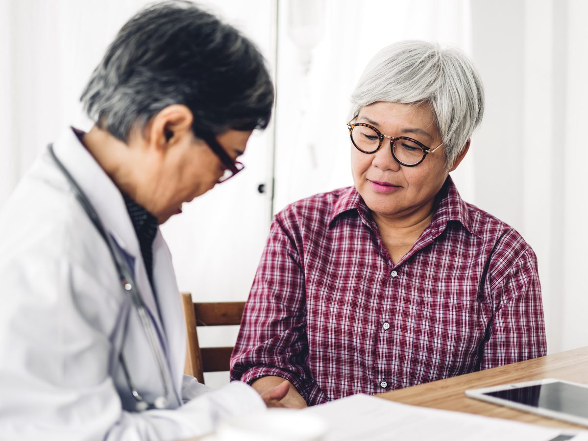 Middle-aged Asian woman with her doctor