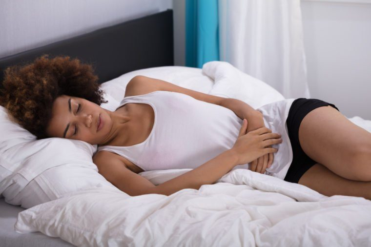 Young Woman Suffering From Stomach Pain Lying On Bed In Bedroom