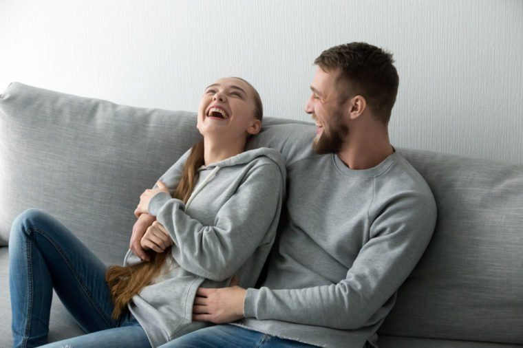 Young happy couple having fun talking laughing relaxing at home on couch, boyfriend embracing girlfriend telling funny joke sitting on sofa, humour in relationships, enjoying weekend together