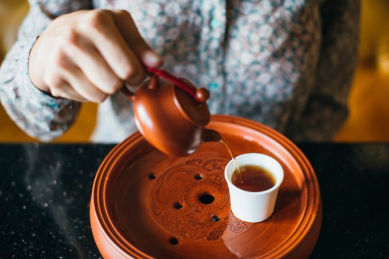 Woman pouring tea into a cup