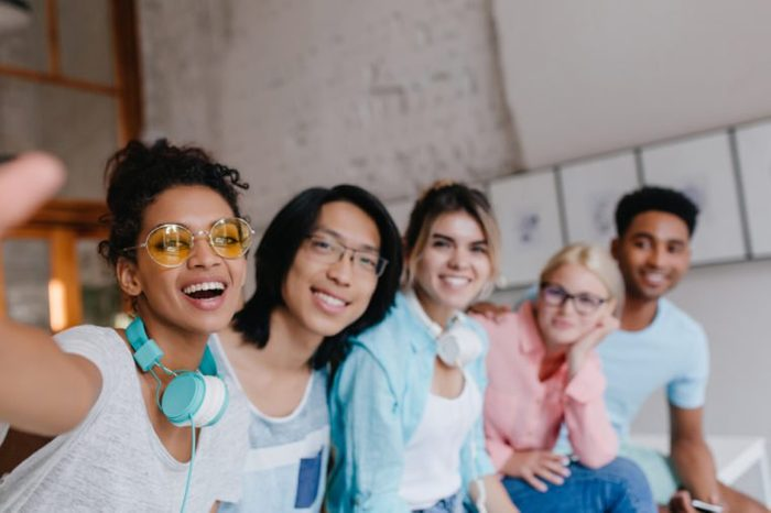 Inspired girl in stylish yellow glasses making selfie with her asian university friend and other students. Charming young woman with light-brown skin taking photo of herself with people on background.