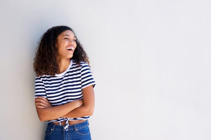 Portrait of happy young african american woman standing against white background