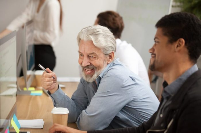 Smiling senior employee discussing email with african colleague at workplace, happy older worker talking to black coworker joking about online computer work, aged and young managers laugh in office