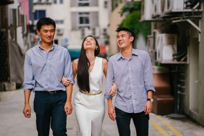 A young, attractive Chinese woman walks along a street in Asia during the day with her arms crossed with two young Chinese men. They are all laughing as they walk.