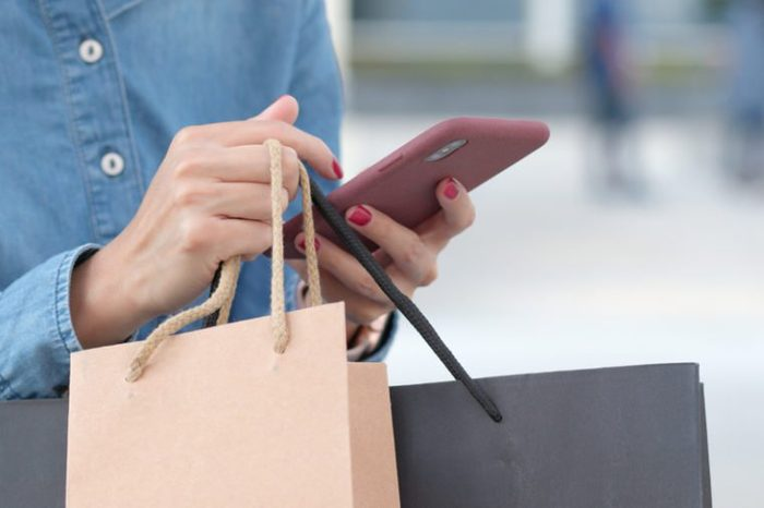 Woman use of mobile phone for shopping with holding shopping bag